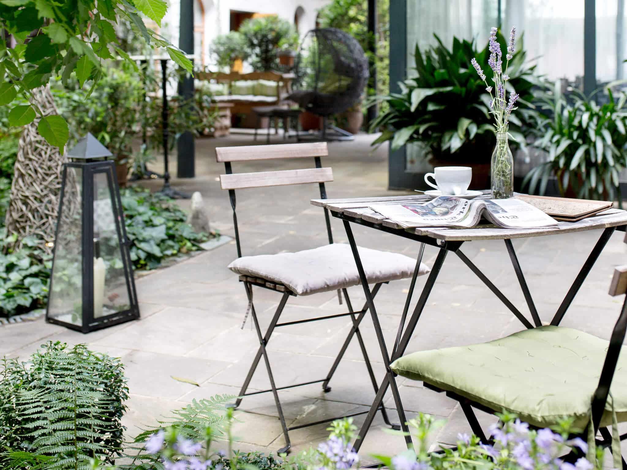 Boutiquehotel Stadthalle Garten mit Zeitung und Kaffee