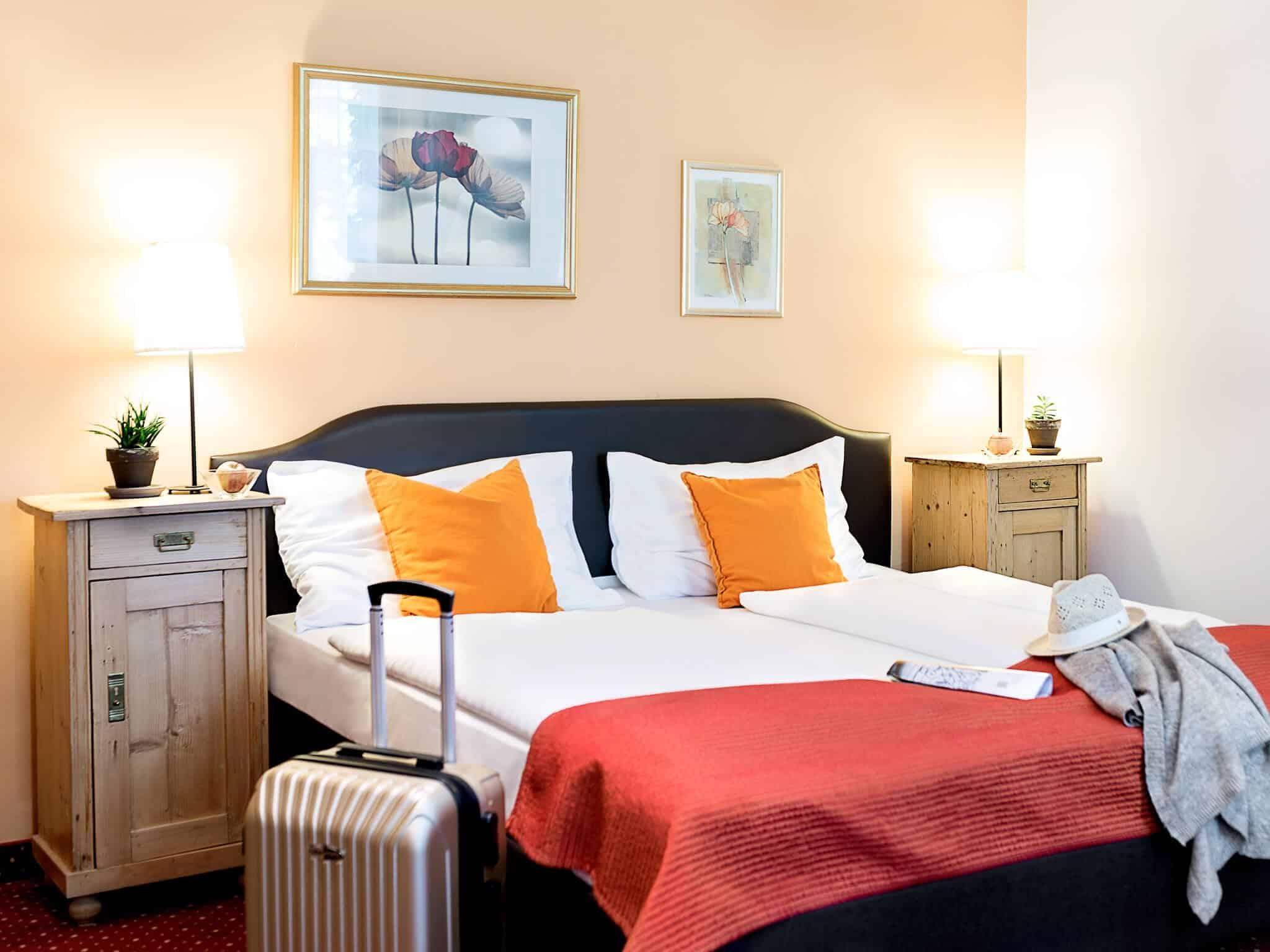 Boutiquehotel Stadthalle Superior Zimmer mit Koffer und Hut am Bett