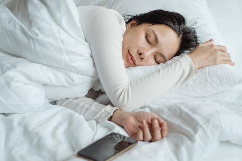 Frau mit Handy im Bett