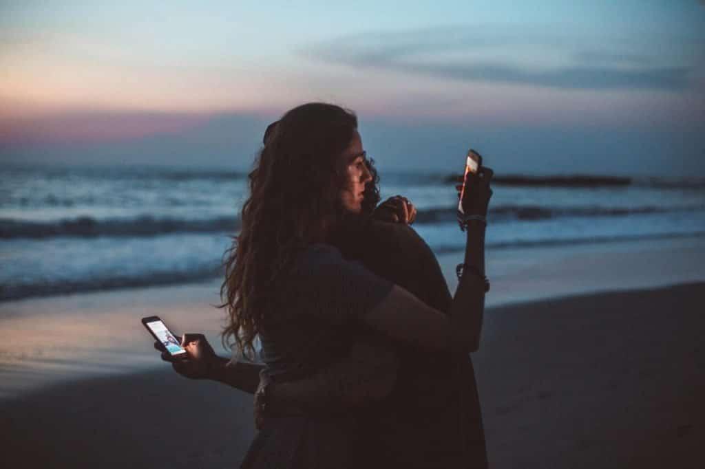 Menschen umarmen sich mit Handy