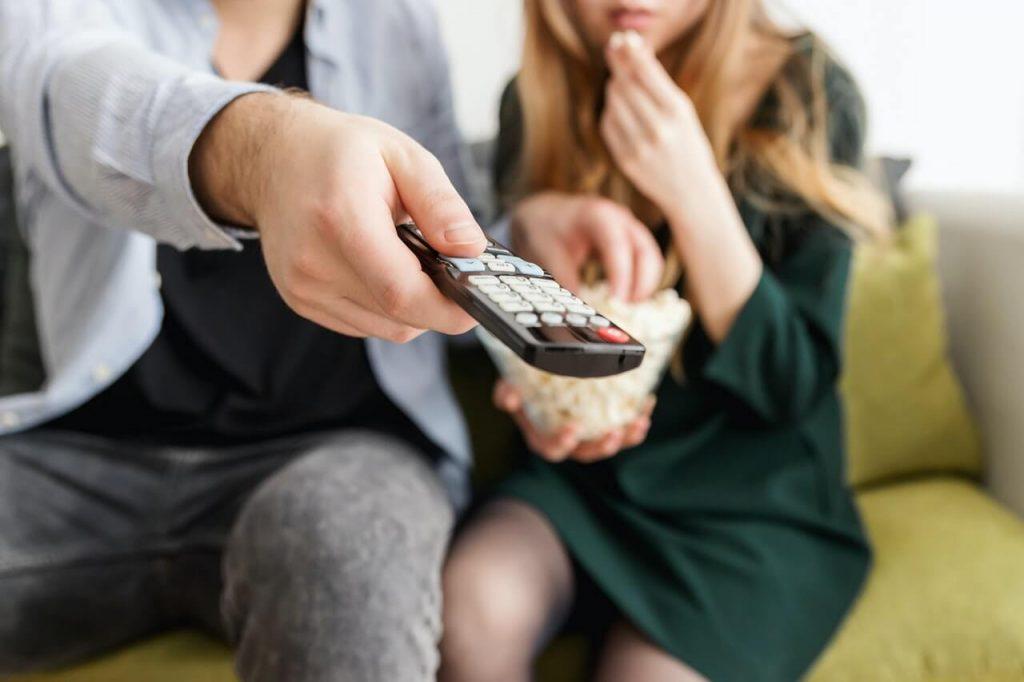 Zwei Menschen am Sofa mit Fernbedienung
