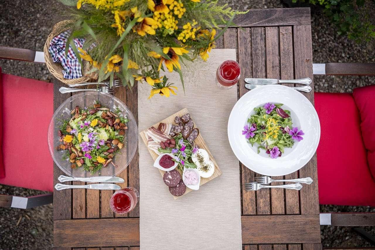 Tisch mit Wildkräutersalten angerichtet und Dirndlbrettel copyright netzwerk Kulinarik pov Umweltzeichen